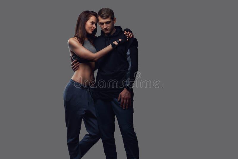Ελκυστικό ζεύγος, λεπτός θηλυκός και όμορφος τύπος brunette sportswear στην αγκαλιά σε ένα στούντιο σε ένα σκοτάδι κατασκευασμένο στοκ φωτογραφίες