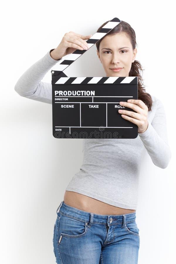 Ελκυστικό θηλυκό χαμόγελο με clapper το χαρτόνι στοκ φωτογραφία με δικαίωμα ελεύθερης χρήσης