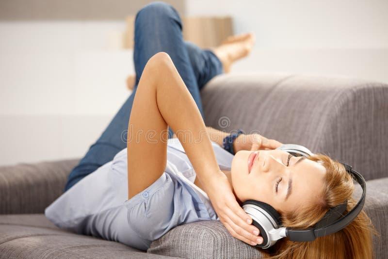 Ελκυστικό κορίτσι που απολαμβάνει τη μουσική που βάζει στον καναπέ στοκ εικόνες