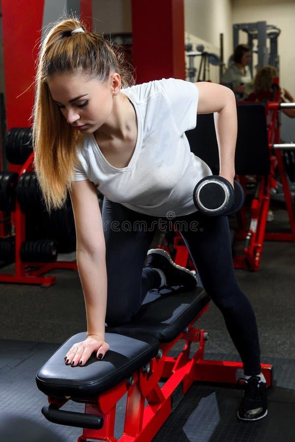 Ελκυστικό κορίτσι που επιλύει ενεργά με τον αλτήρα σε μια γυμναστική στοκ φωτογραφίες