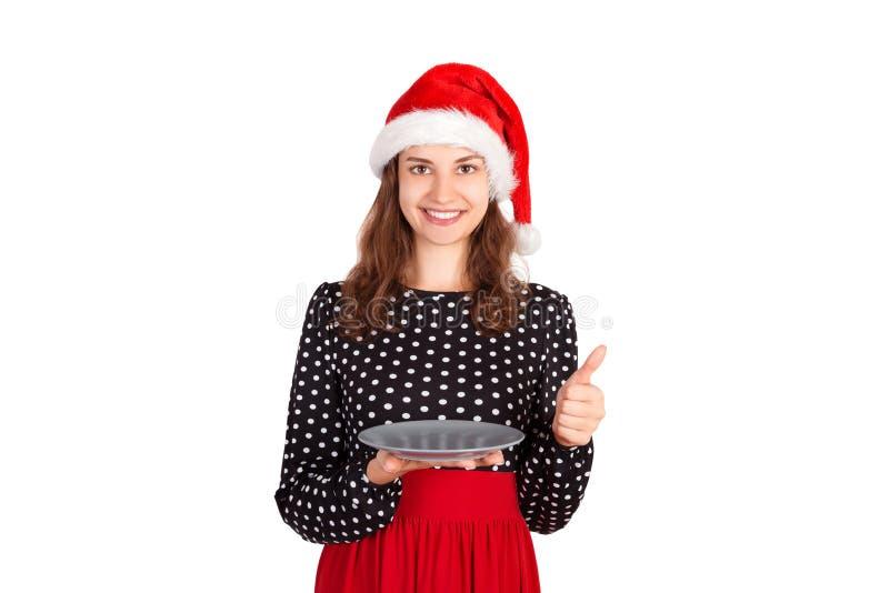 Ελκυστικό κορίτσι που κρατά ένα κενό πιάτο στα χέρια της και που παρουσιάζει αντίχειρες προετοιμαμένος για τις νέες διακοπές έτου στοκ φωτογραφία με δικαίωμα ελεύθερης χρήσης