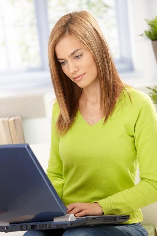 Ελκυστικό κορίτσι που περιοδεύει Διαδίκτυο στο σπίτι σε πράσινο στοκ εικόνες