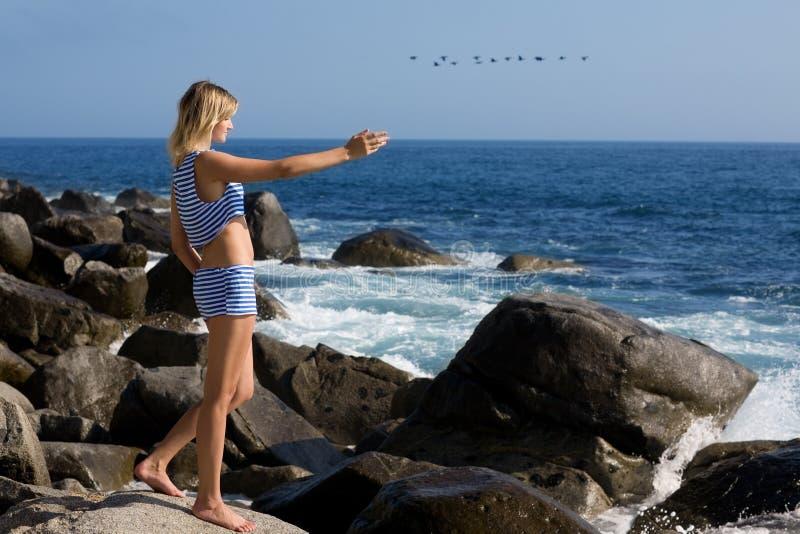 Ελκυστικό κορίτσι που χαλαρώνει τη δύσκολη παραλία θαλασσίως. στοκ εικόνες