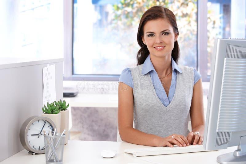 Ελκυστικό κορίτσι που χρησιμοποιεί τον υπολογιστή στην αρχή στοκ εικόνες