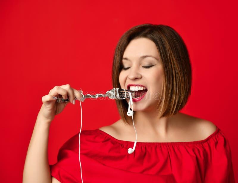 Ελκυστικό κορίτσι στο κόκκινο φόρεμα που κρατά ένα δίκρανο στα χέρια στο βούλωμα ακουστικών προετοιμασμένος για να φάει στοκ εικόνα με δικαίωμα ελεύθερης χρήσης