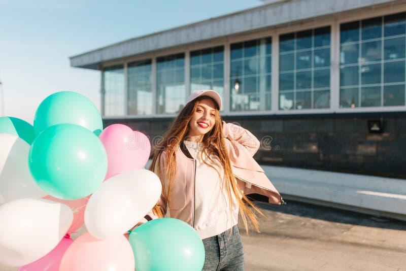 Ελκυστικό κορίτσι brunette με το λαμπρό χαμόγελο που θέτει πρόθυμα τα μπαλόνια ηλίου εκμετάλλευσης μετά από τον περίπατο κατά μήκ στοκ φωτογραφία