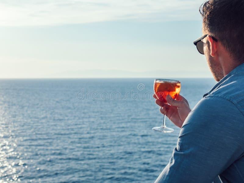 Ελκυστικό, μοντέρνο άτομο στα γυαλιά ηλίου, που κρατούν ένα ποτήρι του όμορφου ρόδινου κοκτέιλ στοκ εικόνες με δικαίωμα ελεύθερης χρήσης