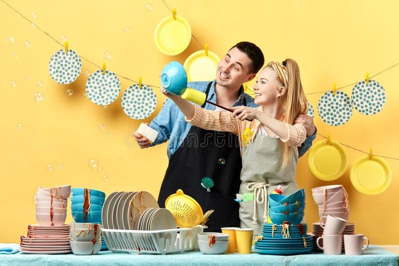 Ελκυστικό νέο ζεύγος που ξεσκονίζει τα πιάτα χόμπι, καθημερινή ρουτίνα στοκ φωτογραφία με δικαίωμα ελεύθερης χρήσης