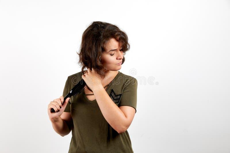 Ελκυστικό νέο θηλυκό brunette στο περιστασιακό χακί πουκάμισο που βουρτσίζει με τη σκοτεινή σγουρή τρίχα χτενών στοκ φωτογραφία