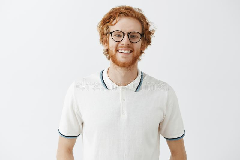 Ελκυστικό νέο και φιλικό redhead άτομο με τη γενειάδα στα μαύρα γυαλιά και το πουκάμισο πόλο που χαμογελά χαρωπά στη κάμερα στοκ φωτογραφία με δικαίωμα ελεύθερης χρήσης