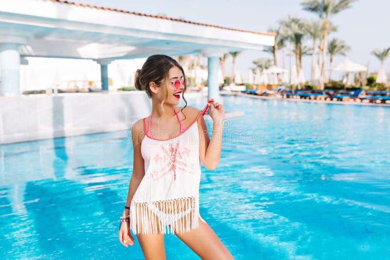 Ελκυστικό νέο κορίτσι στο φόρεμα παραλιών που στέκεται μπροστά από την υπαίθρια λίμνη με τους φοίνικες στο υπόβαθρο και που κοιτά στοκ φωτογραφία
