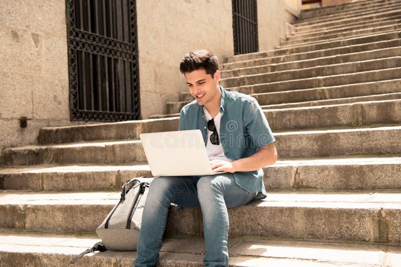 Ελκυστικό νέο σύγχρονο άτομο που εργάζεται με τον υπολογιστή στην πόλη στα εξωτερικά σκαλοπάτια στοκ εικόνα με δικαίωμα ελεύθερης χρήσης