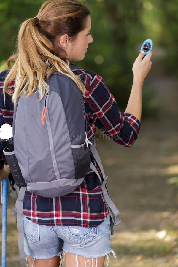 Ελκυστικό ξανθό κορίτσι πορτρέτου που χρησιμοποιεί την πυξίδα υπαίθρια στοκ φωτογραφίες