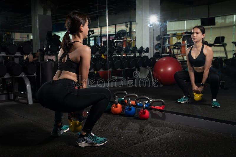 Ελκυστικό ξανθό κορίτσι που κάνει τις ασκήσεις με το κουδούνι κατσαρολών Weightlifting, διαγώνιες τακτοποίηση και δύναμη που ανυψ στοκ εικόνες