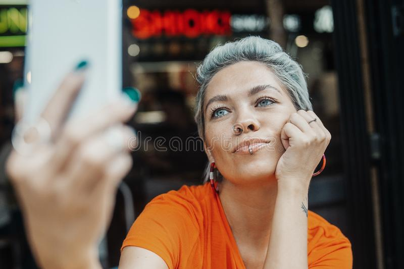 Ελκυστικό ξανθό κορίτσι που κάνει selfie στον καφέ και τον καφέ κατανάλωσης στοκ εικόνα