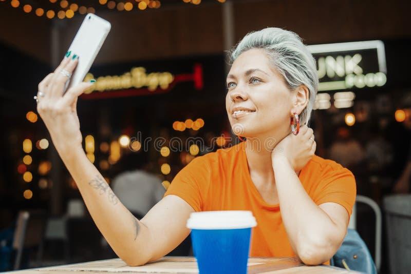 Ελκυστικό ξανθό κορίτσι που κάνει selfie στον καφέ στοκ εικόνες