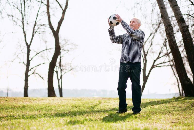 Ελκυστικό ώριμο άτομο που ρίχνει τη σφαίρα στοκ φωτογραφία με δικαίωμα ελεύθερης χρήσης