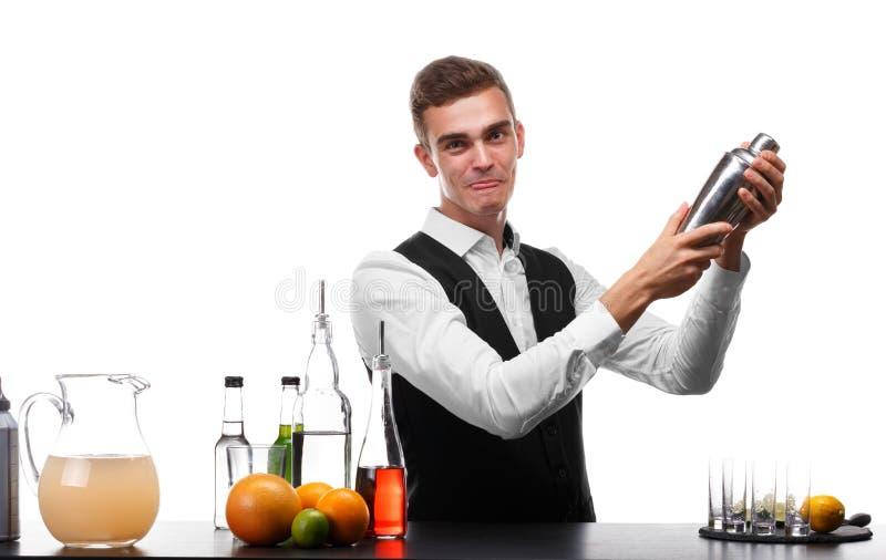 Ελκυστικό bartender με έναν δονητή σε έναν μετρητή φραγμών, ασβέστης, πορτοκάλια, λεμόνια που απομονώνονται σε ένα άσπρο υπόβαθρο στοκ εικόνα
