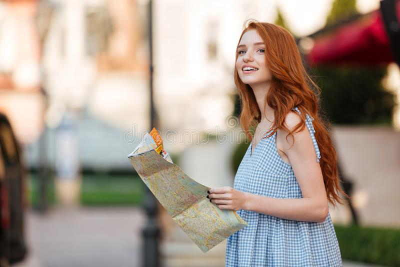 Ελκυστικό redhead κορίτσι που κρατά έναν χάρτη οδηγών στοκ φωτογραφία