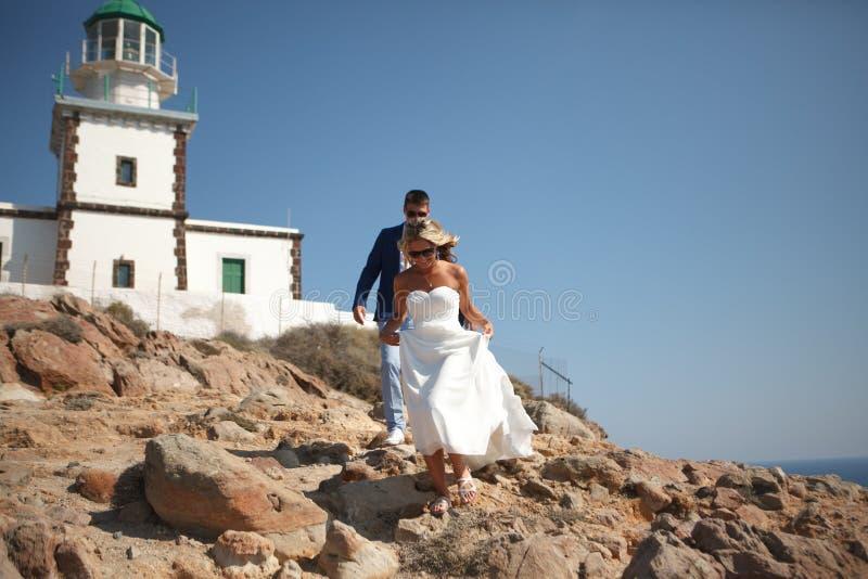 Ελλάδα, Santorini, Oia 16 Σεπτεμβρίου 2014: μερικοί πρόσφατα παντρεμένοι άνθρωποι στην όμορφη ενδυμασία που απολαμβάνουν τους μήν στοκ εικόνα