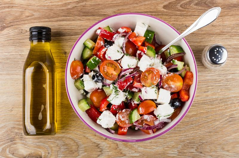 Ελληνικά σαλάτα και κουτάλι στο κύπελλο γυαλιού, μπουκάλι του πετρελαίου στοκ εικόνες