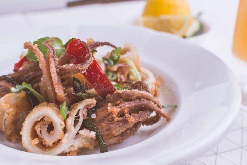 Ελληνικά τηγανισμένα καλαμάρια Calamari με το κόκκινο πιπέρι τσίλι και τη φρέσκια μέντα στοκ φωτογραφίες