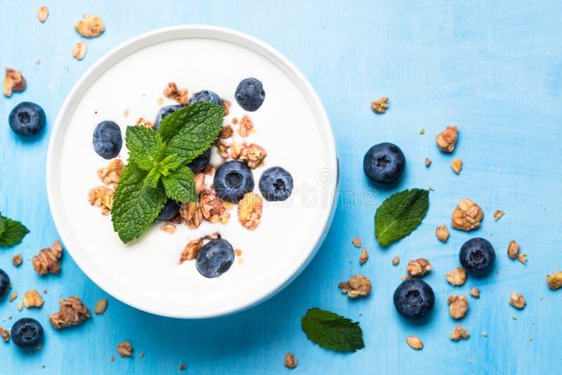 Ελληνικά granola και βακκίνια γιαουρτιού στον μπλε πίνακα στοκ φωτογραφία