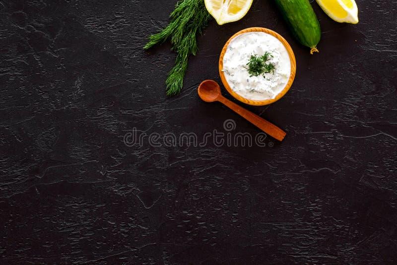 Ελληνική εμβύθιση γιαουρτιού με την πρασινάδα, αγγούρι, πορτοκάλια, σκόρδο στο μαύρο διάστημα αντιγράφων άποψης υποβάθρου τοπ στοκ εικόνες
