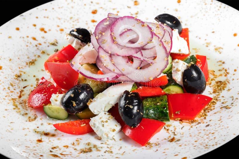 Ελληνική σαλάτα με τα φρέσκα λαχανικά, τις ελιές και το τυρί φέτας στο πιάτο, που απομονώνεται στο μαύρο υπόβαθρο Τοπ όψη στοκ φωτογραφία με δικαίωμα ελεύθερης χρήσης