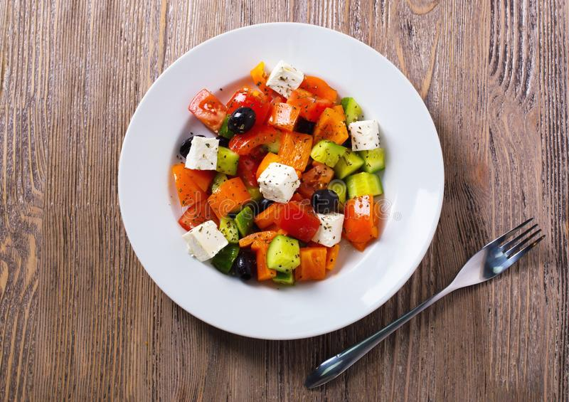 Ελληνική σαλάτα του φρέσκου αγγουριού, της ντομάτας, του γλυκού πιπεριού, του τυριού φέτας και των ελιών με το έλαιο και τα καρυκ στοκ φωτογραφία με δικαίωμα ελεύθερης χρήσης