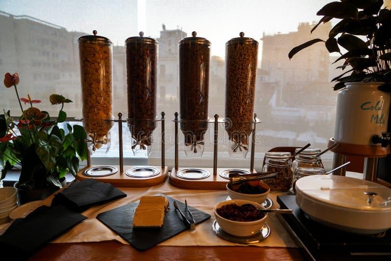 Ελληνικό επιτραπέζιο σύνολο μπουφέδων προγευμάτων με τις ποικιλίες των δημητριακών στη διανομή των πύργων, γιαούρτι, κρύο γάλα, ξ στοκ εικόνα με δικαίωμα ελεύθερης χρήσης