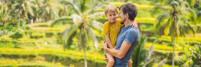 ΕΜΒΛΗΜΑ, ΜΑΚΡΙΟΙ μπαμπάς ΣΧΗΜΑΤΟΣ και ταξιδιώτες γιων στα όμορφα πεζούλια ρυζιού στα πλαίσια των διάσημων ηφαιστείων στο Μπαλί στοκ εικόνα