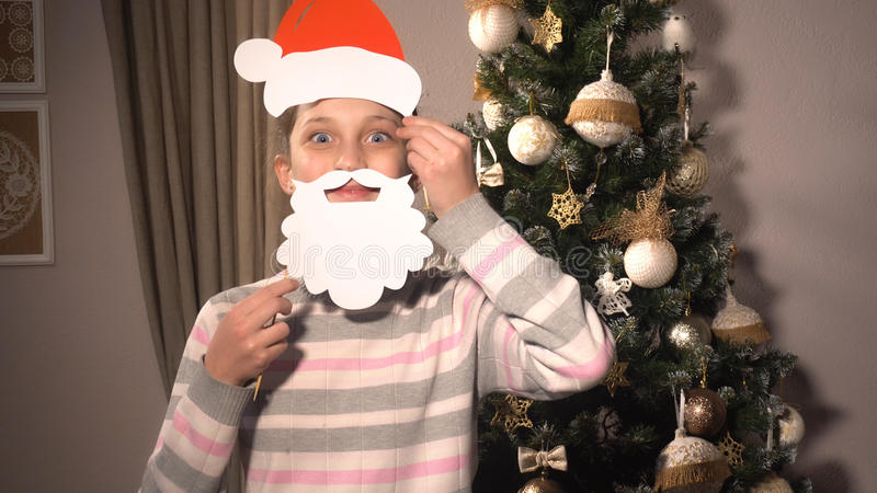 Εμβλήματα εκμετάλλευσης κοριτσιών με το καπέλο και τη γενειάδα Santa ` s στοκ φωτογραφία