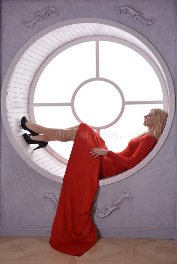 Εμπαθές κορίτσι στο κόκκινο φόρεμα με ανοικτό πίσω από το παράθυρο στοκ φωτογραφίες