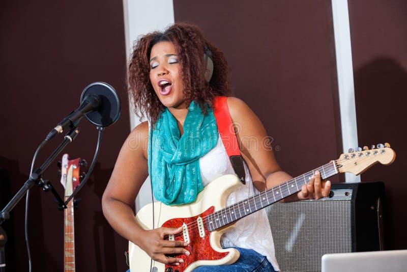 Εμπαθής θηλυκή κιθάρα παιχνιδιού τραγουδιστών στοκ φωτογραφίες με δικαίωμα ελεύθερης χρήσης