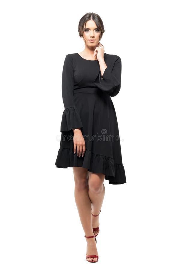 Εμπαθής ισπανική γυναίκα στο μαύρο φόρεμα με το χέρι σχετικά με το λαιμό που εξετάζει τη κάμερα στοκ φωτογραφία