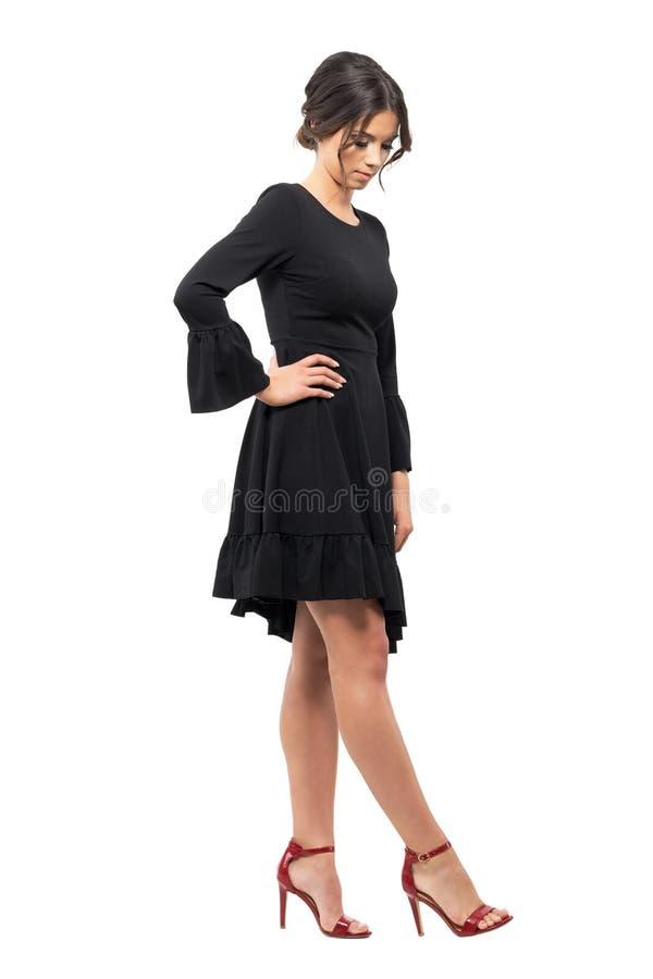 Εμπαθής νέος λατινικός θηλυκός χορευτής που εξετάζει κάτω τα παπούτσια στοκ εικόνα