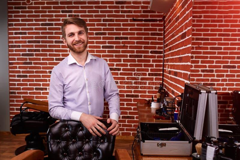 Εμπειρογνώμονας κουρέων που χαμογελά και που εξετάζει τη κάμερα και που κρατά το χέρι στην καρέκλα στεμένος στο barbershop ενάντι στοκ φωτογραφίες