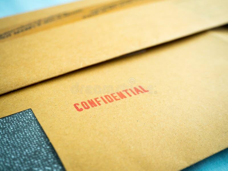 Εμπιστευτικός που τυπώνεται στον καφετή εκλεκτής ποιότητας φάκελο, στη μακροεντολή στοκ φωτογραφία με δικαίωμα ελεύθερης χρήσης
