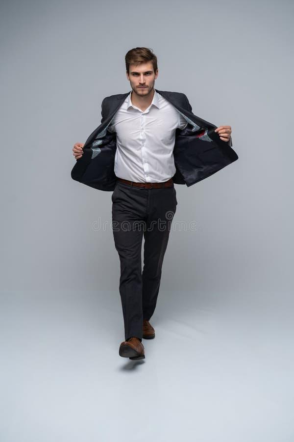 Εμπιστοσύνη σε κάθε κίνηση Πλήρες μήκος του όμορφου νεαρού άνδρα στο πλήρες κοστούμι που το σακάκι του περπατώντας μπροστά επάνω στοκ εικόνα