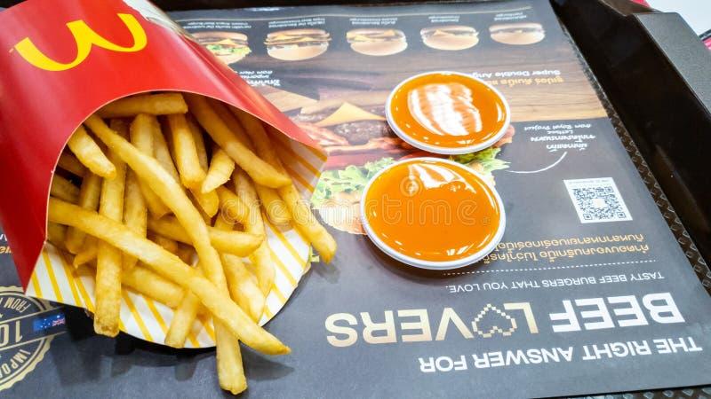 Εμπορευματοκιβώτιο τηγανιτών πατατών στην κόκκινη σάλτσα συσκευασίας και τσίλι στη διαφήμιση του εγγράφου στο χαλί δίσκων στον κα στοκ εικόνες