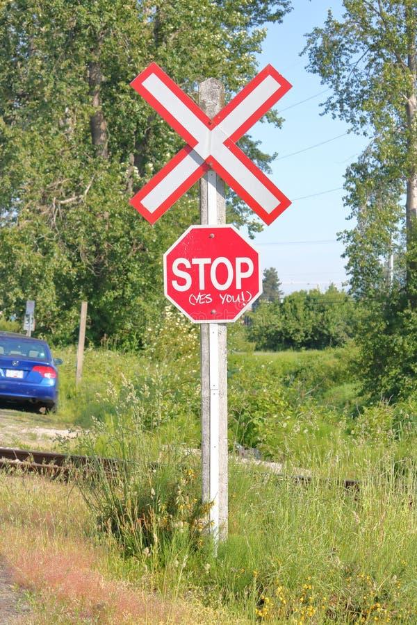 Εμφατικά σημάδι στάσεων και πέρασμα σιδηροδρόμων στοκ εικόνα