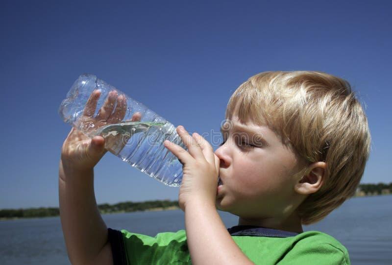 εμφιαλωμένο πόσιμο νερό αγοριών στοκ εικόνες