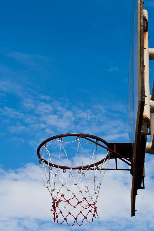 ενάντια στην μπλε στεφάνη καλαθοσφαίρισης ραχών ο ουρανός του στοκ εικόνες