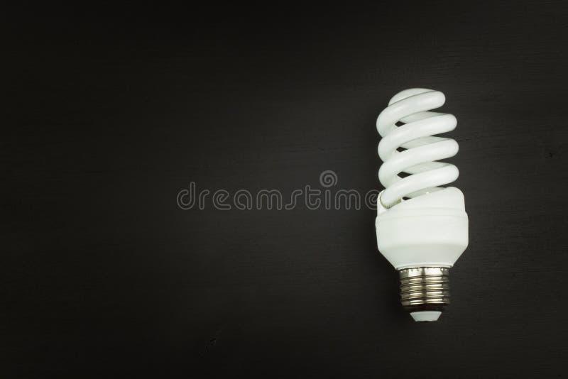 Ενέργεια - λαμπτήρας αποταμίευσης στο μαύρο ξύλινο υπόβαθρο Πωλήσεις των λαμπών φωτός Διαφήμιση για τους βολβούς εξοικονόμησης εν στοκ εικόνες