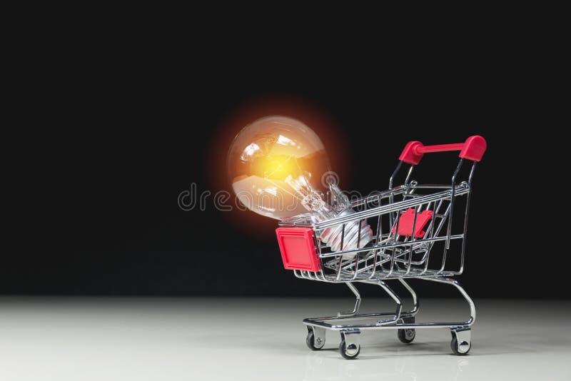 Ενέργεια - λάμπα φωτός αποταμίευσης με τους σωρούς των νομισμάτων και του κάρρου αγορών απεικόνιση αποθεμάτων