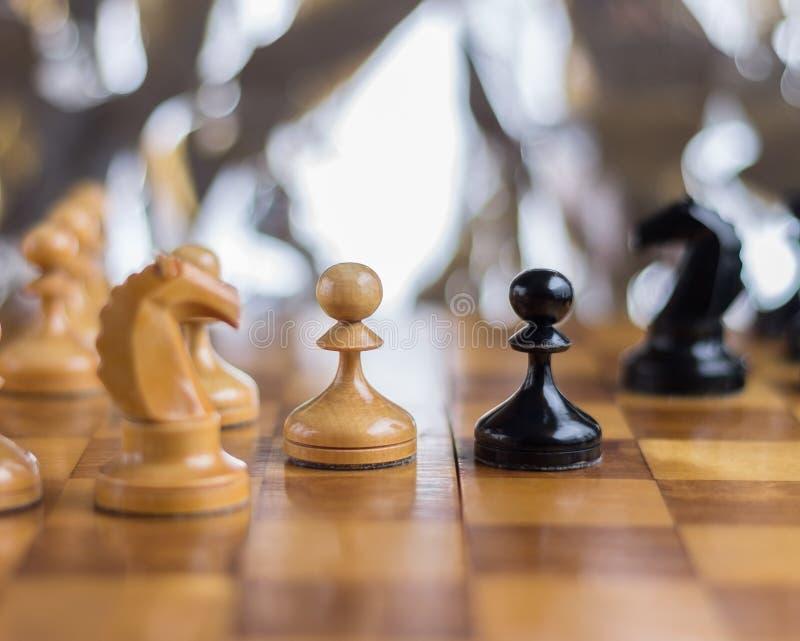 Ενέχυρα που μένουν ο ένας εναντίον του άλλου στον πίνακα σκακιού στοκ εικόνες