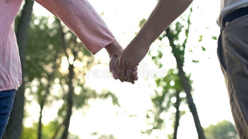 Ενήλικα χέρια εκμετάλλευσης ζευγών που περπατούν στο πάρκο, μαζί μέσω των δυσκολιών ζωής στοκ φωτογραφία με δικαίωμα ελεύθερης χρήσης
