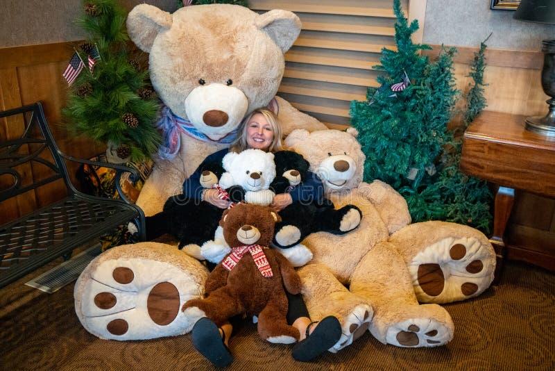Ενήλικες θηλυκές αγκαλιές με μια δέσμη των γιγαντιαίων teddy αρκούδων στοκ εικόνες