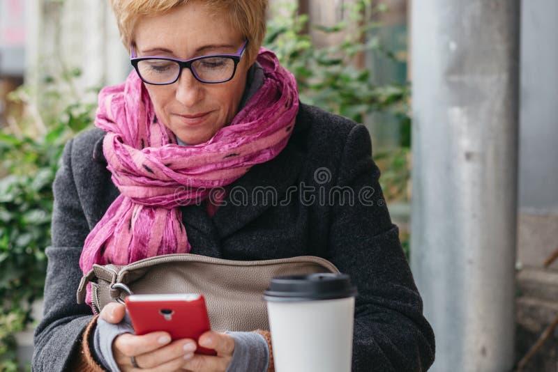 Ενήλικη γυναίκα με τον καφέ και το smartphone στοκ φωτογραφίες